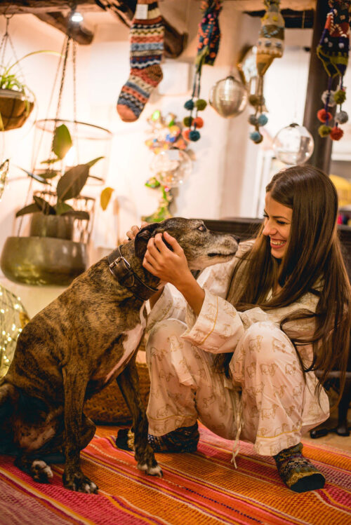 girl wearing cow print pyjamas cuddling a dog