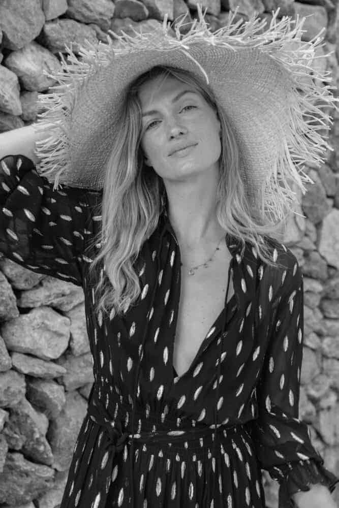 black and white photo of a girl in a sun hatL