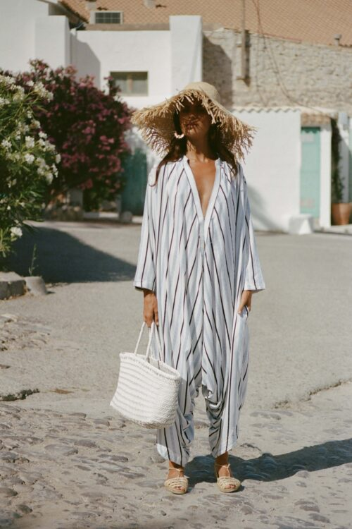 oversized striped jumpsuit paired with a white leather bag