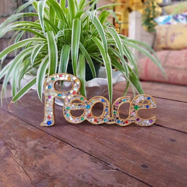 a wooden sign of the word peace in gold glitter
